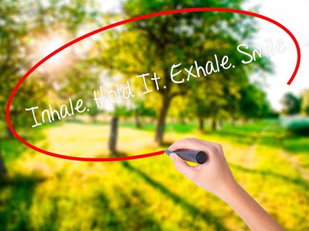 Woman Hand Writing Inhale Hold It Exhale Smile on blank transparent board with a marker isolated over green field background. Business concept. Stock Photo