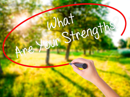 firmeza: Woman Hand Writing What Are Your Strengths? on blank transparent board with a marker isolated over green field background. Business concept. Stock Photo