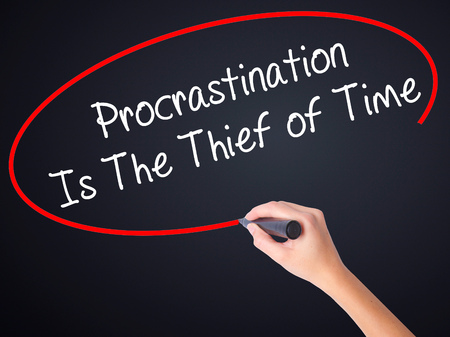 Woman Hand Writing  Procrastination Is The Thief of Time on blank transparent board with a marker isolated over black background. Business concept. Stock Photo Stock Photo