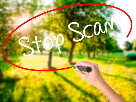 technology transaction: Woman Hand Writing Stop Scam on blank transparent board with a marker isolated over green field background. Stock Photo