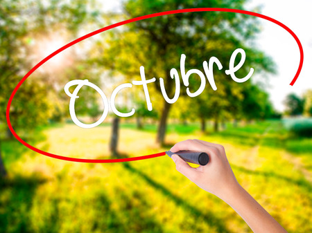 "Woman Hand Writing ""Octubre"" (In Spanish: October) on blank transparent board with a marker isolated over green field background. Business concept. Stock Photo"