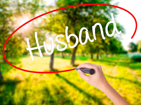 ex wife: Woman Hand Writing Husband on blank transparent board with a marker isolated over green field background. Stock Photo