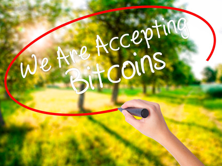 technology transaction: Woman Hand Writing We Are Accepting Bitcoins on blank transparent board with a marker isolated over green field background. Business concept. Stock Photo Stock Photo