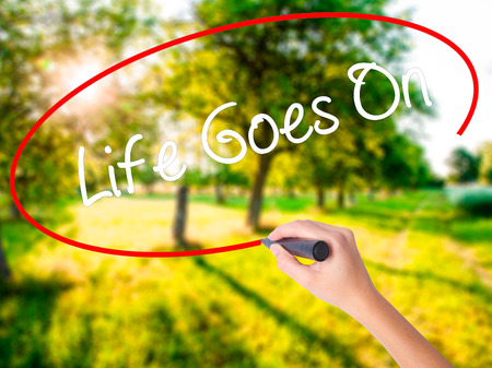Woman Hand Writing Life Goes On on blank transparent board with a marker isolated over green field background. Business concept. Stock Photo Stock Photo