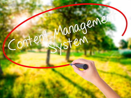 Woman Hand Writing Content Management System  on blank transparent board with a marker isolated over green field background. Business concept. Stock Photo