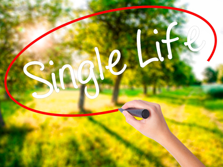 Woman Hand Writing Single Life on blank transparent board with a marker isolated over green field background. Business concept. Stock Photo Stock Photo