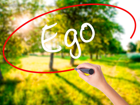 Woman Hand Writing Ego on blank transparent board with a marker isolated over green field background. Stock Photo