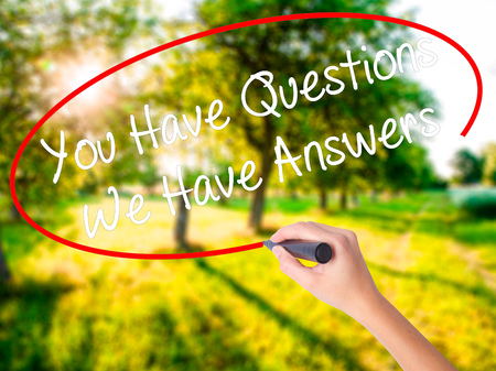 Woman Hand Writing You Have Questions We Have Answers on blank transparent board with a marker isolated over green field background. Business concept. Stock Photo