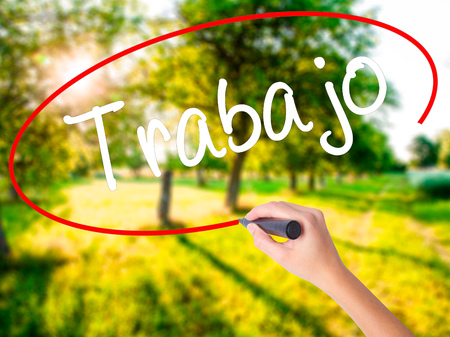 Woman Hand Writing Trabajo  ( work in Spanish) on blank transparent board with a marker isolated over green field background. Stock Photo
