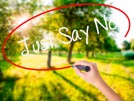 demonstrator: Woman Hand Writing Just Say No on blank transparent board with a marker isolated over green field background. Business concept. Stock Photo