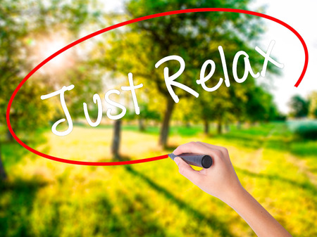 breathe easy: Woman Hand Writing Just Relax on blank transparent board with a marker isolated over green field background. Stock Photo