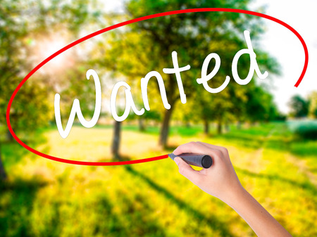Woman Hand Writing Wanted on blank transparent board with a marker isolated over green field background. Stock Photo