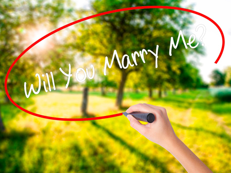 Woman Hand Writing Will You Marry Me? on blank transparent board with a marker isolated over green field background. Stock Photo