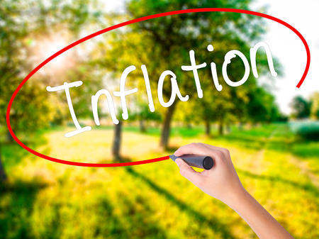 economic theory: Woman Hand Writing Inflation on blank transparent board with a marker isolated over green field background. Stock Photo