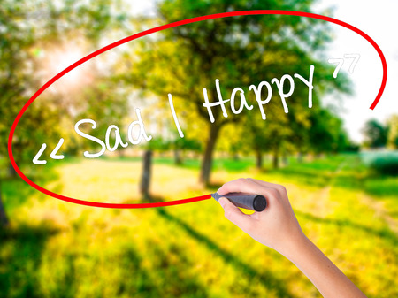 Woman Hand Writing Sad - Happy on blank transparent board with a marker isolated over green field background. Stock Photo