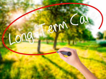 Woman Hand Writing Long-Term Care on blank transparent board with a marker isolated over green field background. Business concept. Stock Photo
