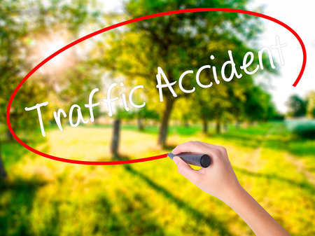 Woman Hand Writing Traffic Accident on blank transparent board with a marker isolated over green field background. Stock Photo