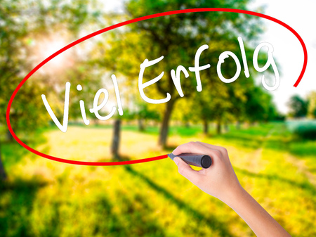 Woman Hand Writing Viel Erfolg (Much Success In German) on blank transparent board with a marker isolated over green field background. Stock Photo