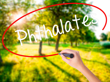 nontoxic: Woman Hand Writing  Phthalates  on blank transparent board with a marker isolated over green field background. Stock Photo