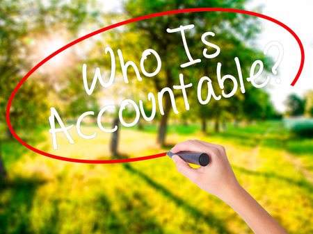 Woman Hand Writing Who Is Accountable? on blank transparent board with a marker isolated over green field background. Business concept. Stock Photo