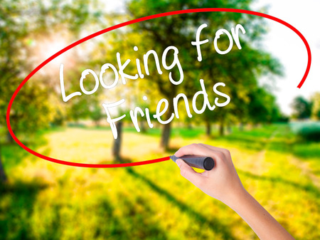 Woman Hand Writing Looking for Friends on blank transparent board with a marker isolated over green field background. Stock Photo Stock Photo