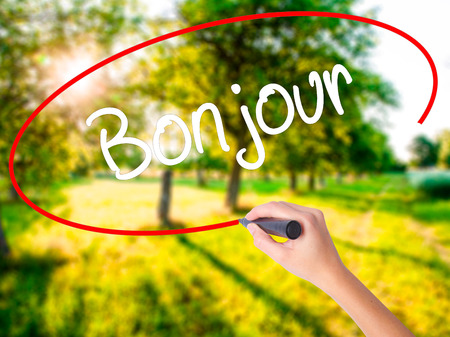 bonjour: Woman Hand Writing Bonjour  (Good Morning in French) on blank transparent board with a marker isolated over green field background. Stock Photo
