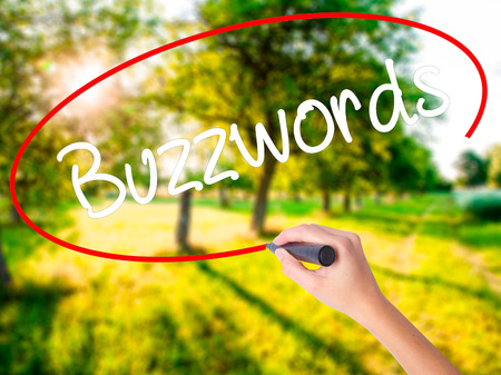 Woman Hand Writing Buzzwords on blank transparent board with a marker isolated over green field background. Stock Photo