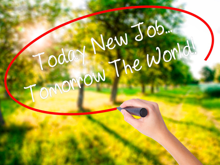 Woman Hand Writing Today New Job. Tomorrow The World! on blank transparent board with a marker isolated over green field background. Stock Photo