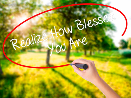 realize: Woman Hand Writing  Realize How Blessed You Are  on blank transparent board with a marker isolated over green field background. Business concept. Stock Photo