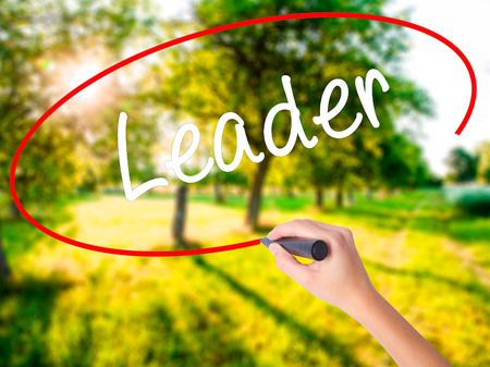 Woman Hand Writing Leader on blank transparent board with a marker isolated over green field background. Stock Photo