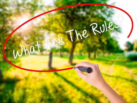 Woman Hand Writing What Are The Rules?  on blank transparent board with a marker isolated over green field background. Business concept. Stock Photo