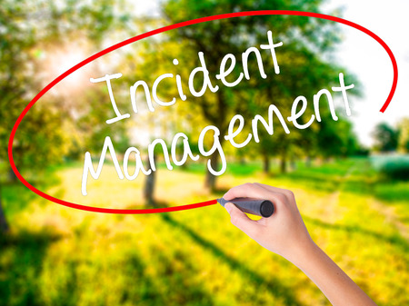 iscp: Woman Hand Writing Incident Management on blank transparent board with a marker isolated over green field background. Business concept. Stock Photo
