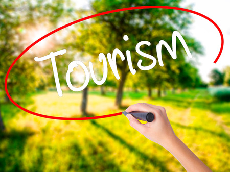 Woman Hand Writing Tourism  on blank transparent board with a marker isolated over green field background. Stock Photo Stock Photo