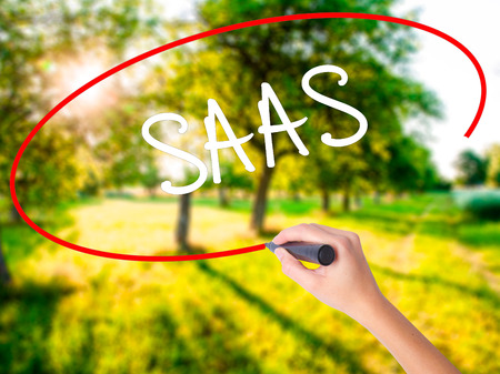 Woman Hand Writing SAAS on blank transparent board with a marker isolated over green field background. Stock Photo Stock Photo