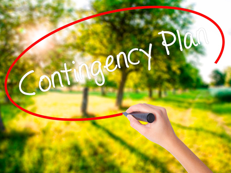 contingency: Woman Hand Writing Contingency Plan on blank transparent board with a marker isolated over green field background. Stock Photo