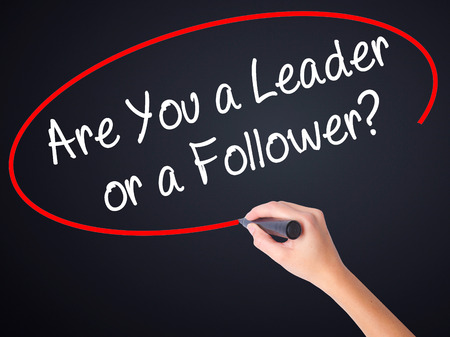 blindly: Woman Hand Writing Are You a Leader or a Follower? on blank transparent board with a marker isolated over black background. Business concept. Stock Photo