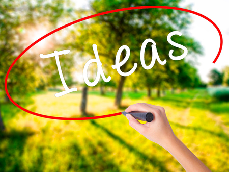 opinions: Woman Hand Writing Ideas on blank transparent board with a marker isolated over green field background. Business concept. Stock Photo