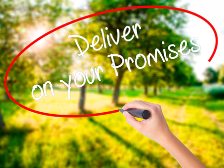 Woman Hand Writing Deliver on your Promises on blank transparent board with a marker isolated over green field background. Stock Photo