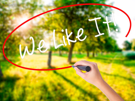 Woman Hand Writing We Like It! on blank transparent board with a marker isolated over green field background. Stock Photo Stock Photo
