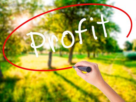 rate of return: Woman Hand Writing Profit on blank transparent board with a marker isolated over green field background. Business concept. Stock Photo