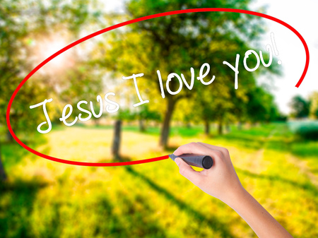 religious clothing: Woman Hand Writing Jesus I love you! on blank transparent board with a marker isolated over green field background. Business concept. Stock Photo