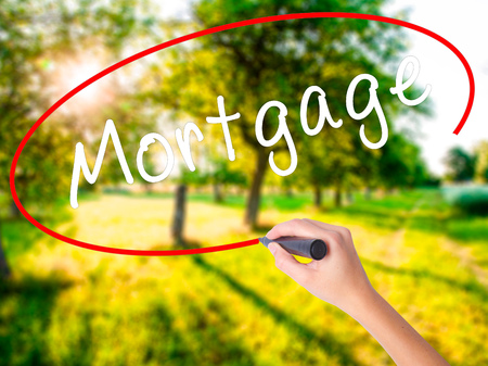 Woman Hand Writing Mortgage on blank transparent board with a marker isolated over green field background. Business concept. Stock Photo Stock Photo