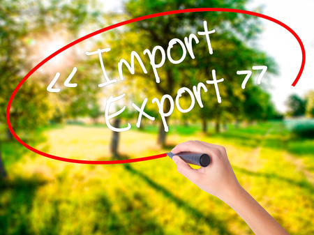 Woman Hand Writing Import - Export on blank transparent board with a marker isolated over green field background. Stock Photo