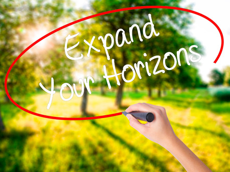 Woman Hand Writing  Expand Your Horizons  on blank transparent board with a marker isolated over green field background. Stock Photo