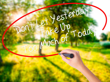 Woman Hand Writing Dont Let Yesterday Take Up Too Much of Today on blank transparent board with a marker isolated over green field background. Stock Photo