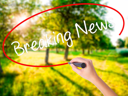 Woman Hand Writing Breaking News on blank transparent board with a marker isolated over green field background. Business concept. Stock Photo