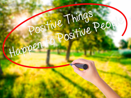 Woman Hand Writing Positive Things Happen to Positive People on blank transparent board with a marker isolated over green field background. Business concept. Stock Photo