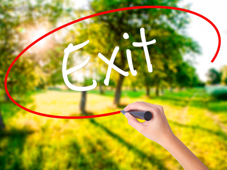 Woman Hand Writing Exit on blank transparent board with a marker isolated over green field background. Stock Photo