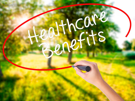 Woman Hand Writing Healthcare Benefits on blank transparent board with a marker isolated over green field background. Business concept. Stock Photo