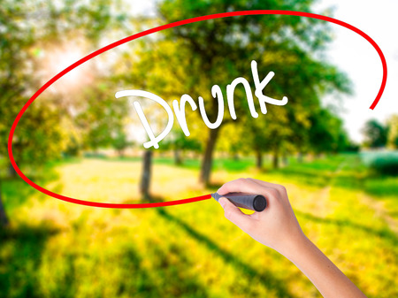 Woman Hand Writing Drunk on blank transparent board with a marker isolated over green field background. Business concept. Stock Photo